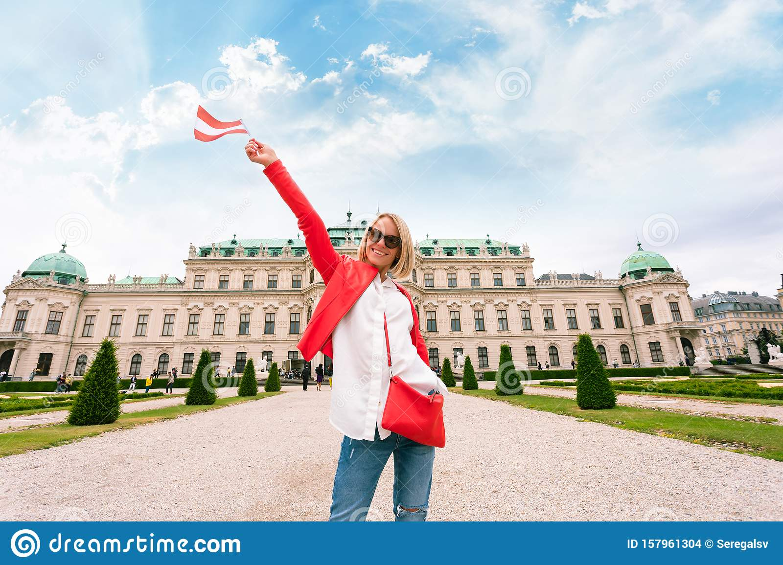 Female traveler with the flag of Austria against the backdrop of the Upper Belvedere Palace in Vienna.