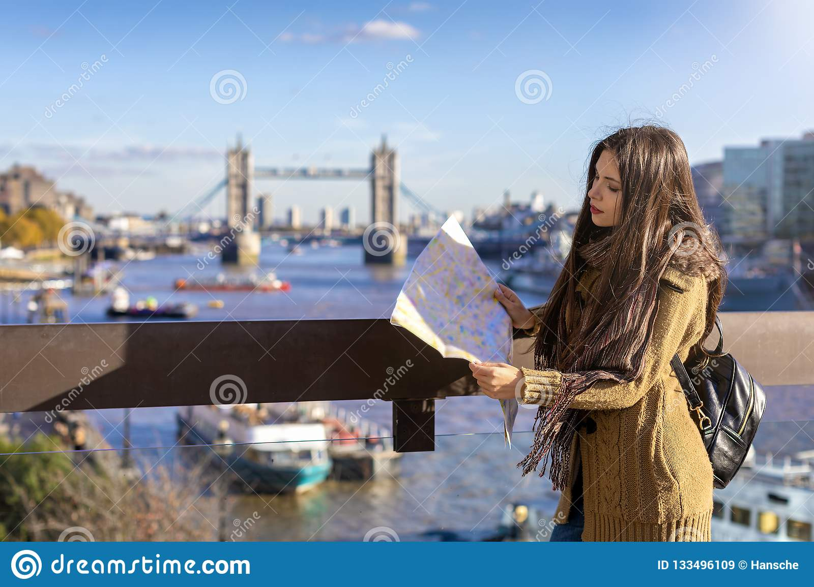 Female traveler looks at the street map in front of the Tower Bridge in London, UK