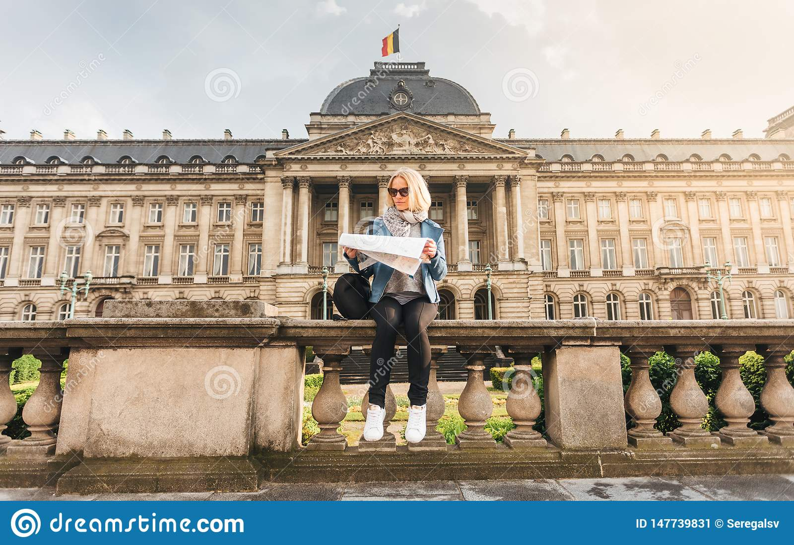 Female traveler sits on the parapet on the background of the Royal Palace in Brussels and looks into the map, Belgium