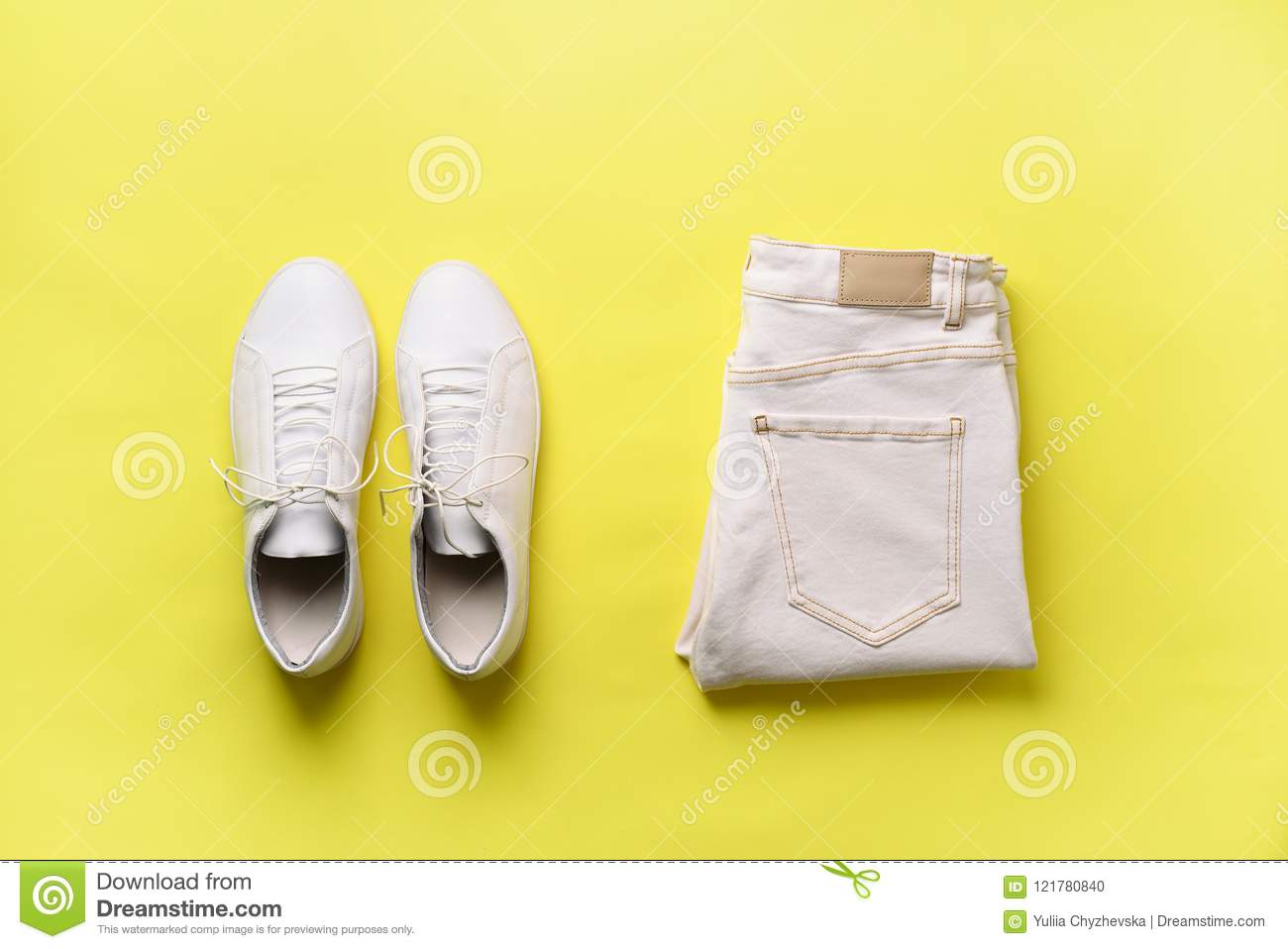 Female white sneakers and jeans on yellow background with copy space. Top view. Summer fashion, shopping, capsule
