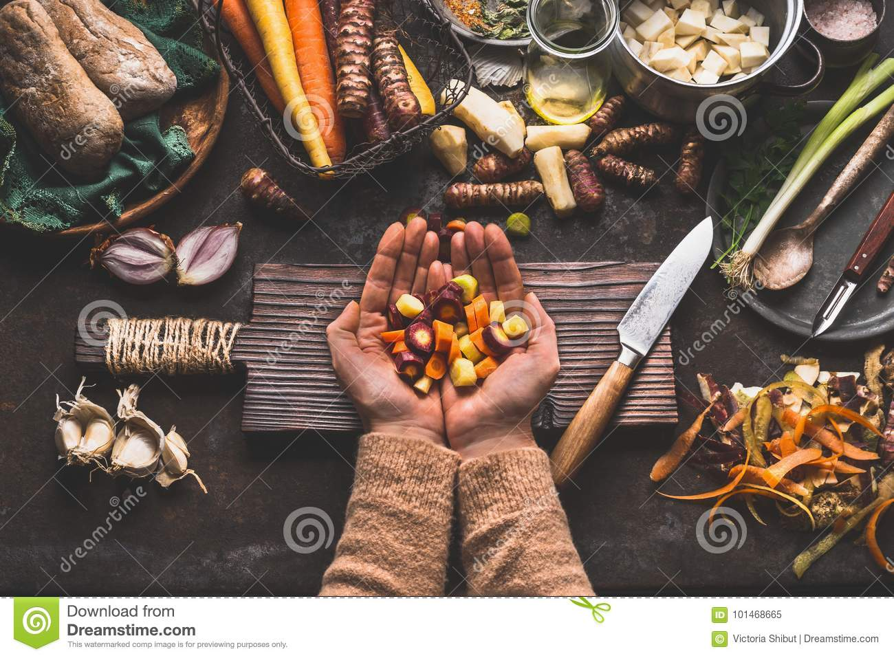 Female woman hands holding diced colorful vegetables on rustic kitchen table with vegetarian cooking ingredients and tools. Health