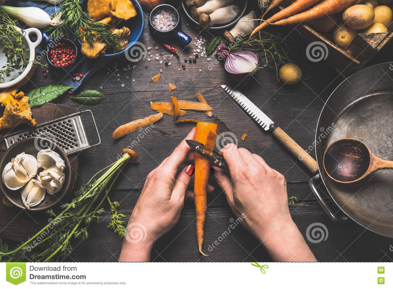 Female woman hands peeling carrots on dark wooden kitchen table with vegetables cooking ingredients