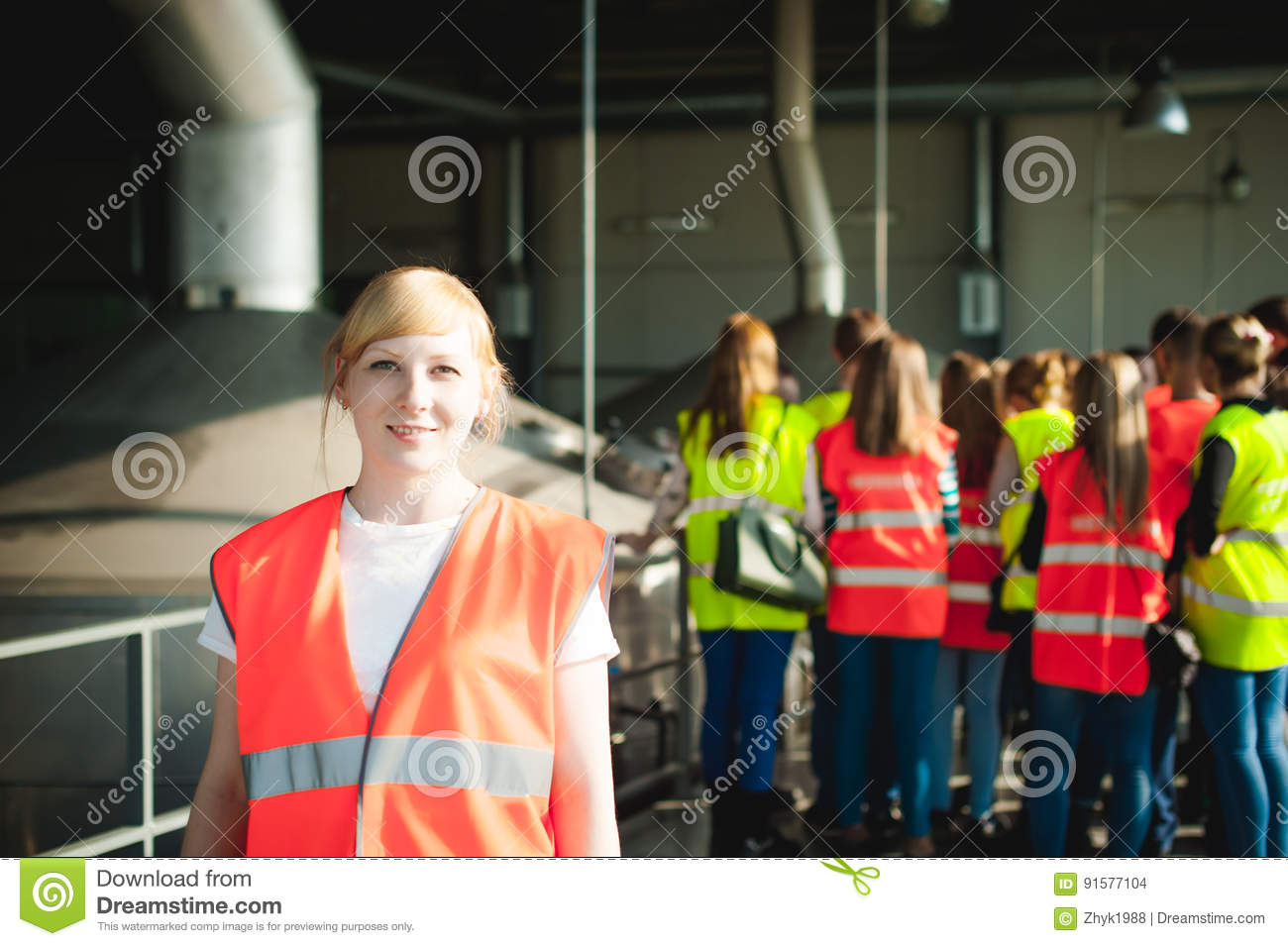 Female worker on beer factory. portrait woman in robe, standing on background line Food production, Inspection management control