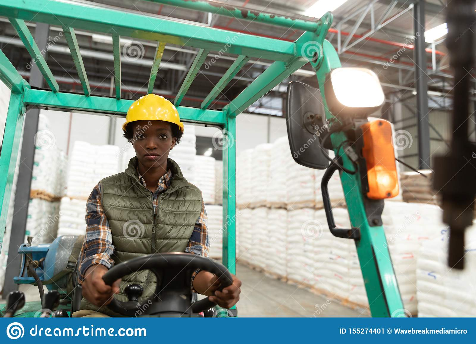 Female worker looking at camera while driving forklift in warehouse