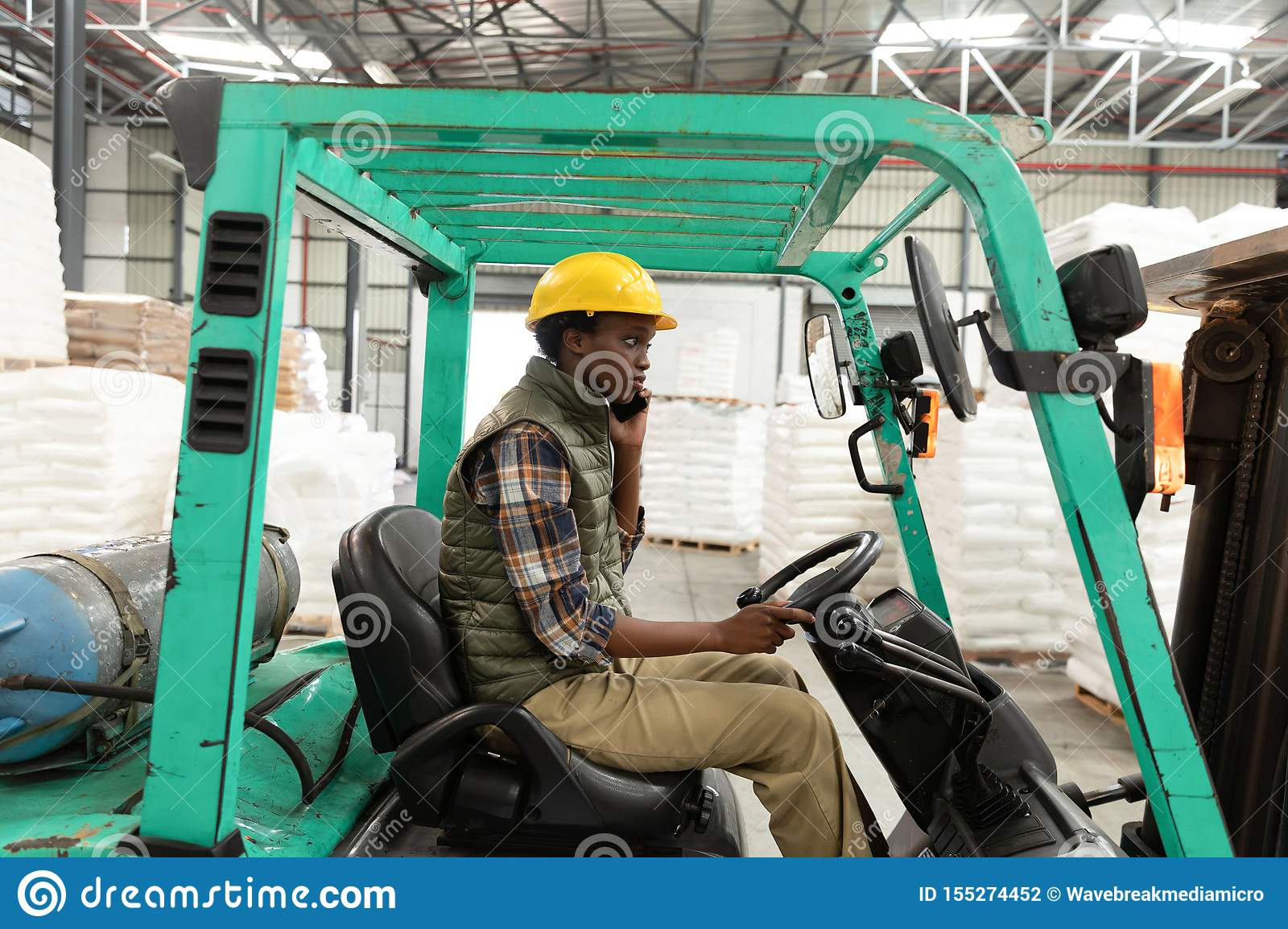 Female worker talking on mobile phone while driving forklift in warehouse