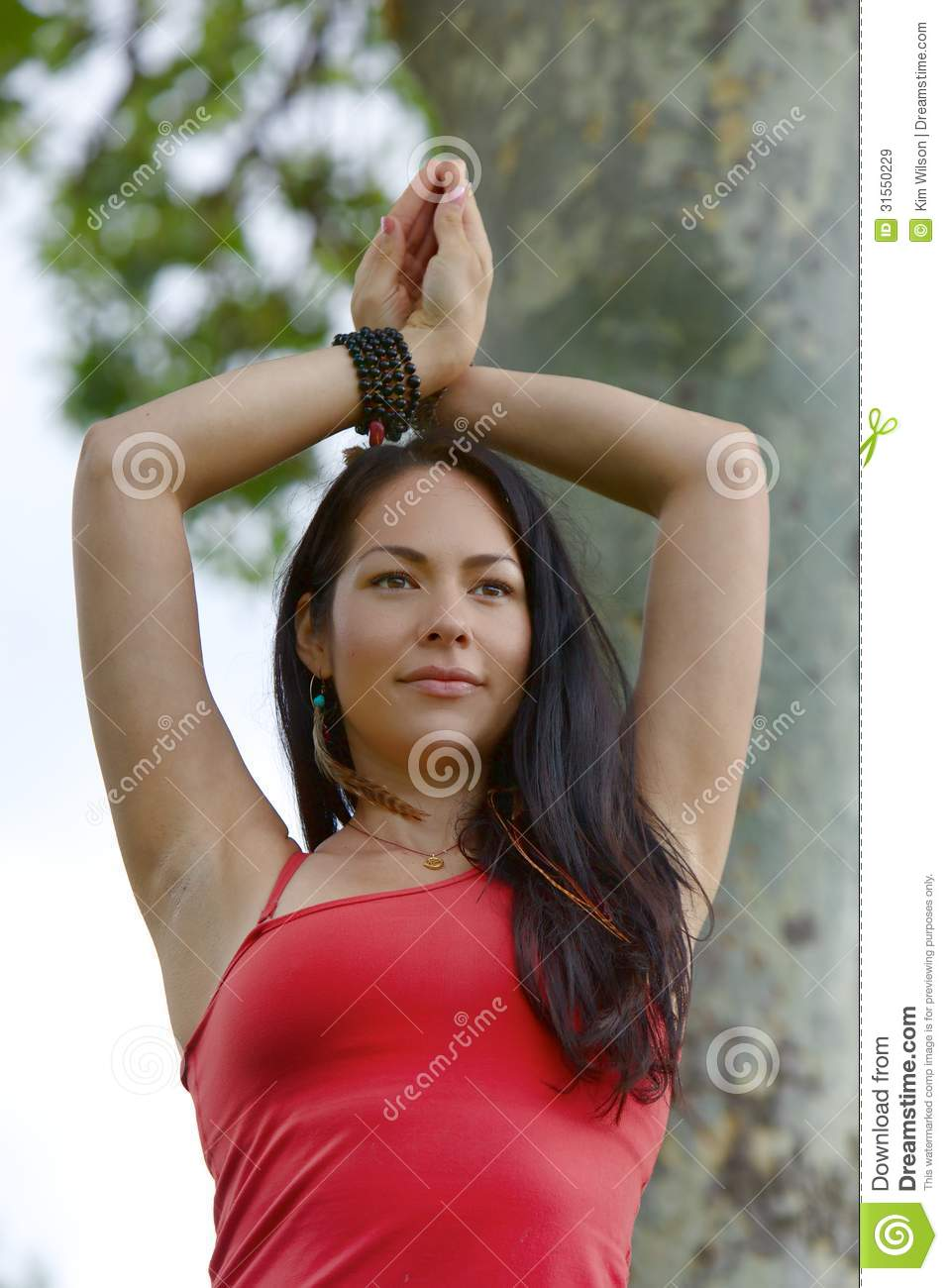 Female Yogi Stands With Hands Crossed Above Her Head ...