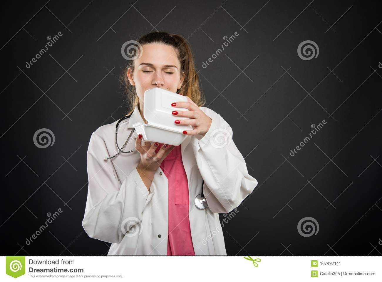 Female Young Doctor Smelling Lunch Box Stock Image - Image