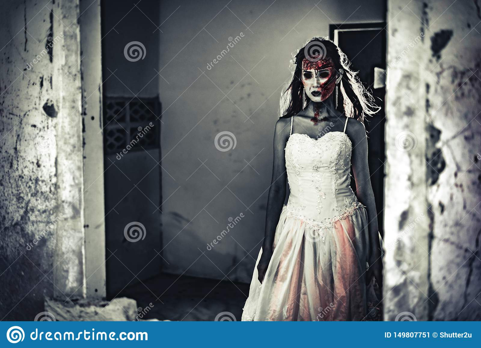 Female zombie corpse standing in front of grunge wall in abandoned house. Horror and Ghost concept. Halloween day festival and