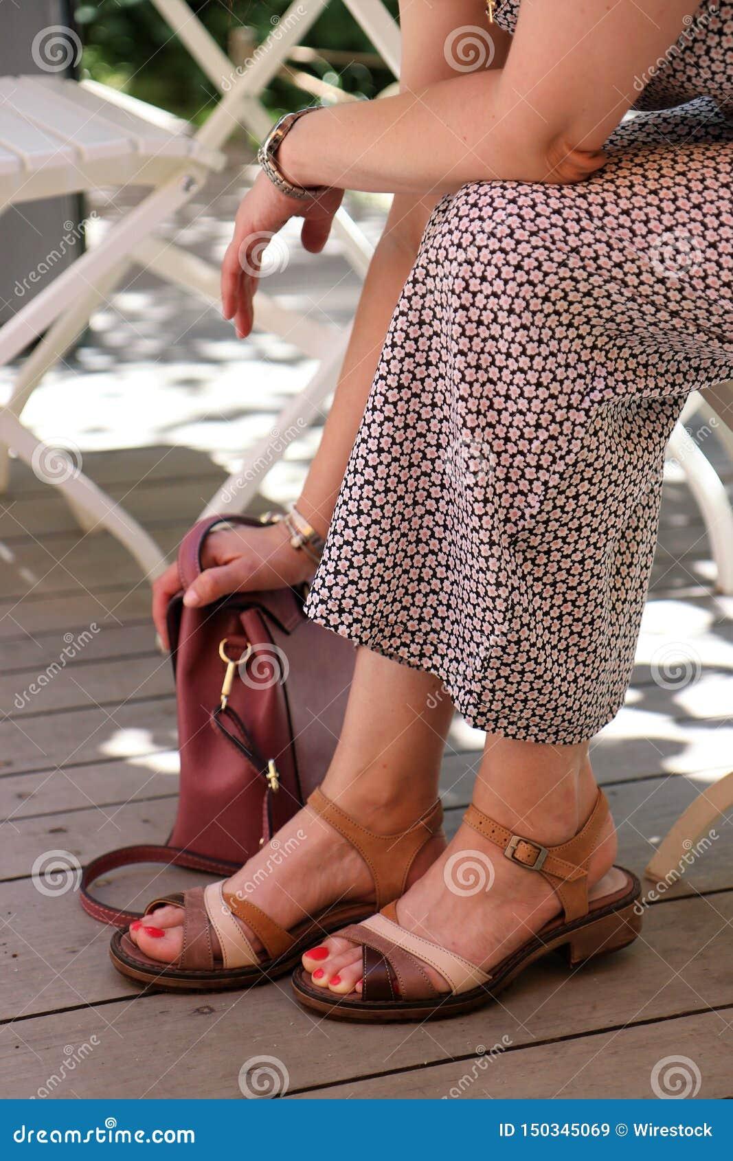 Femelle dans une robe se reposant avec sa main sur son sac