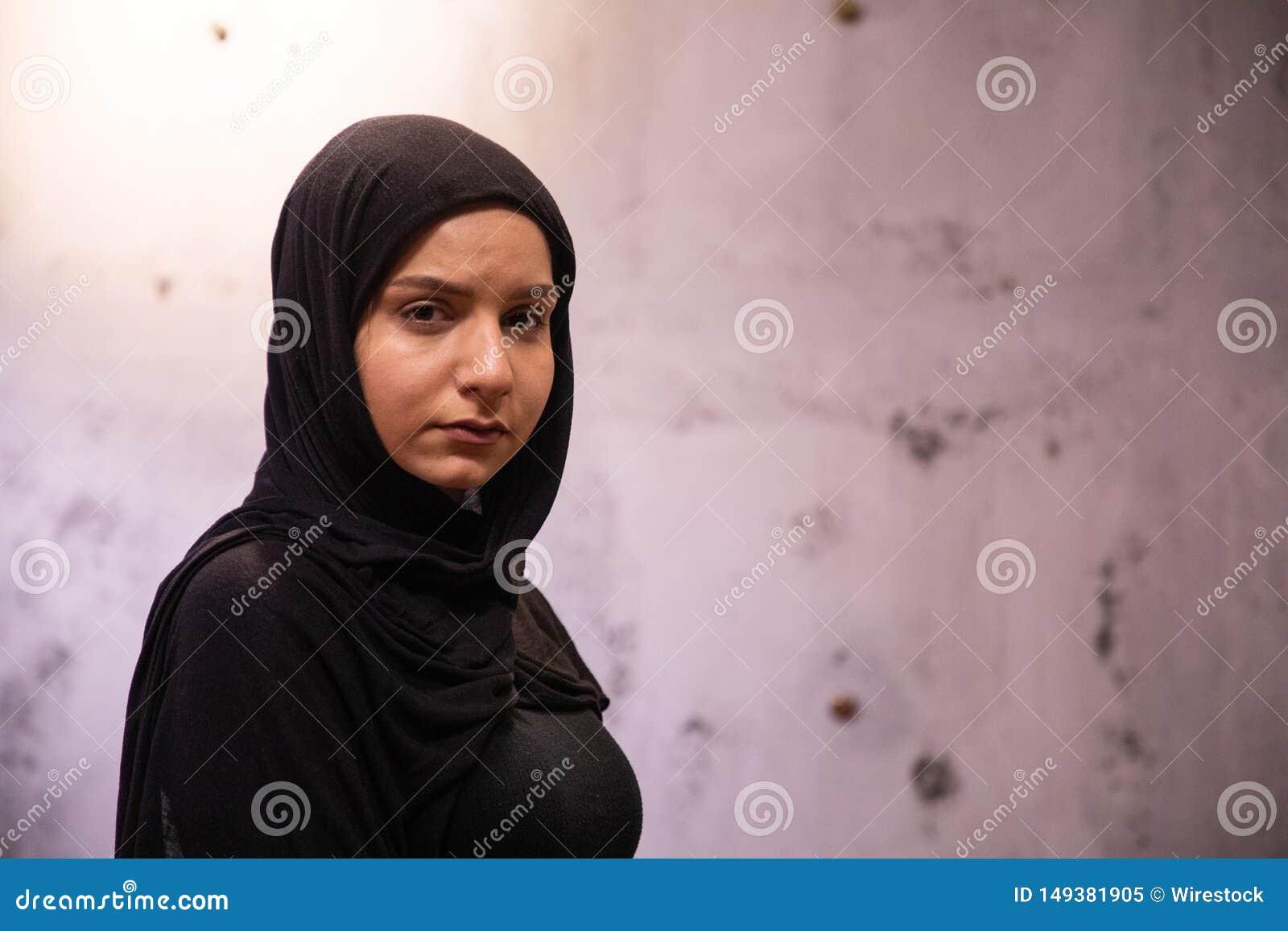 Femelle musulmane attirante afflig?e dans un hijab noir avec un mur endommag? sale ? l arri?re-plan