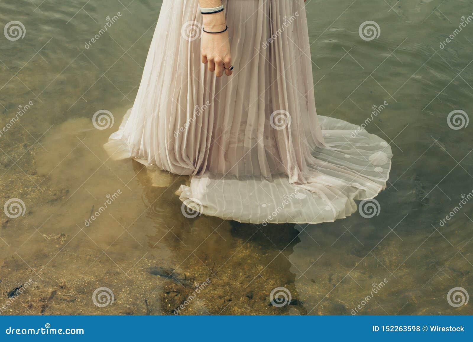 Femelle portant une longue position de robe de robe dans l eau