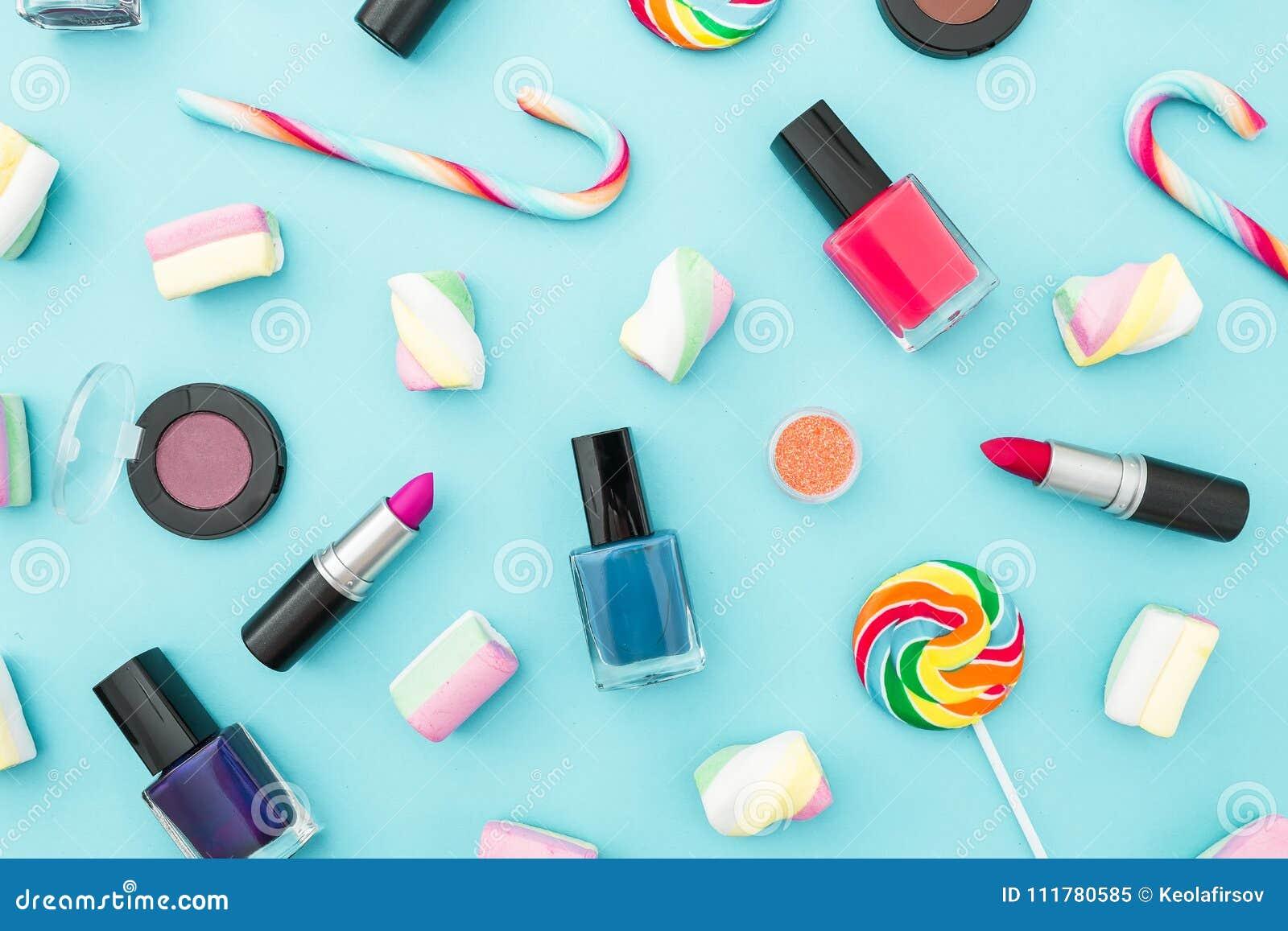 Feminine cosmetics and bright sugar candy on blue pastel background. Top view. Flat lay. Creativity feminine desk.
