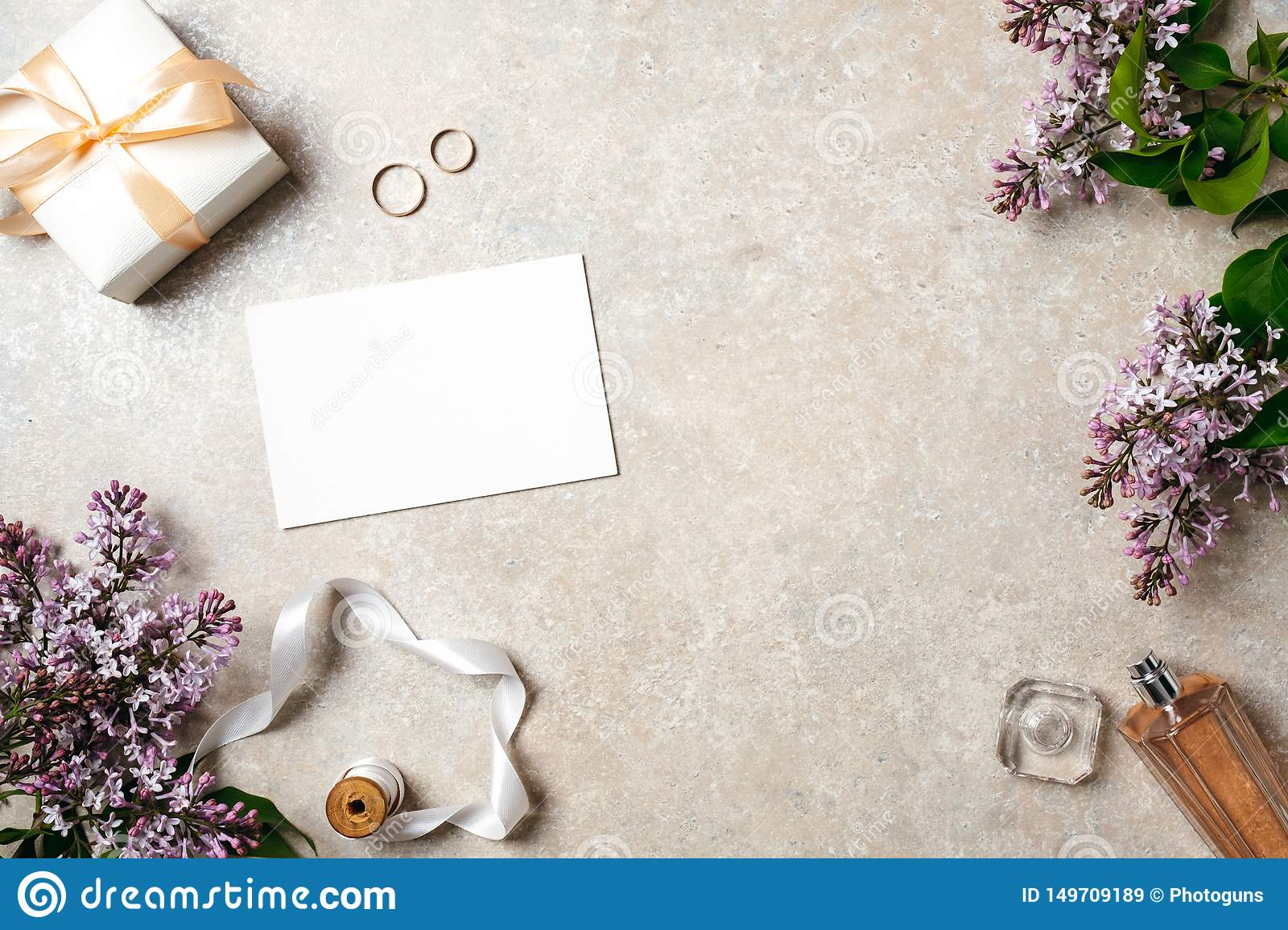Feminine desk with wedding accessories, blank paper card, rings and spring lilac flowers. Wedding concept, invitation card mock up