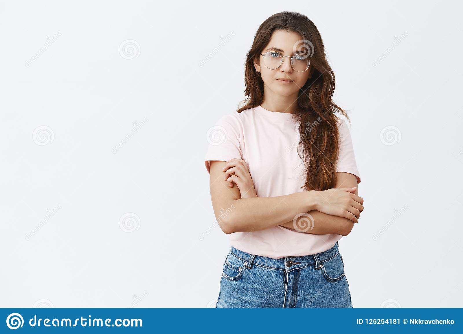 Feminine good-looking and smart female journalist in trendy glasses holding hands crossed on chest and smiling broadly