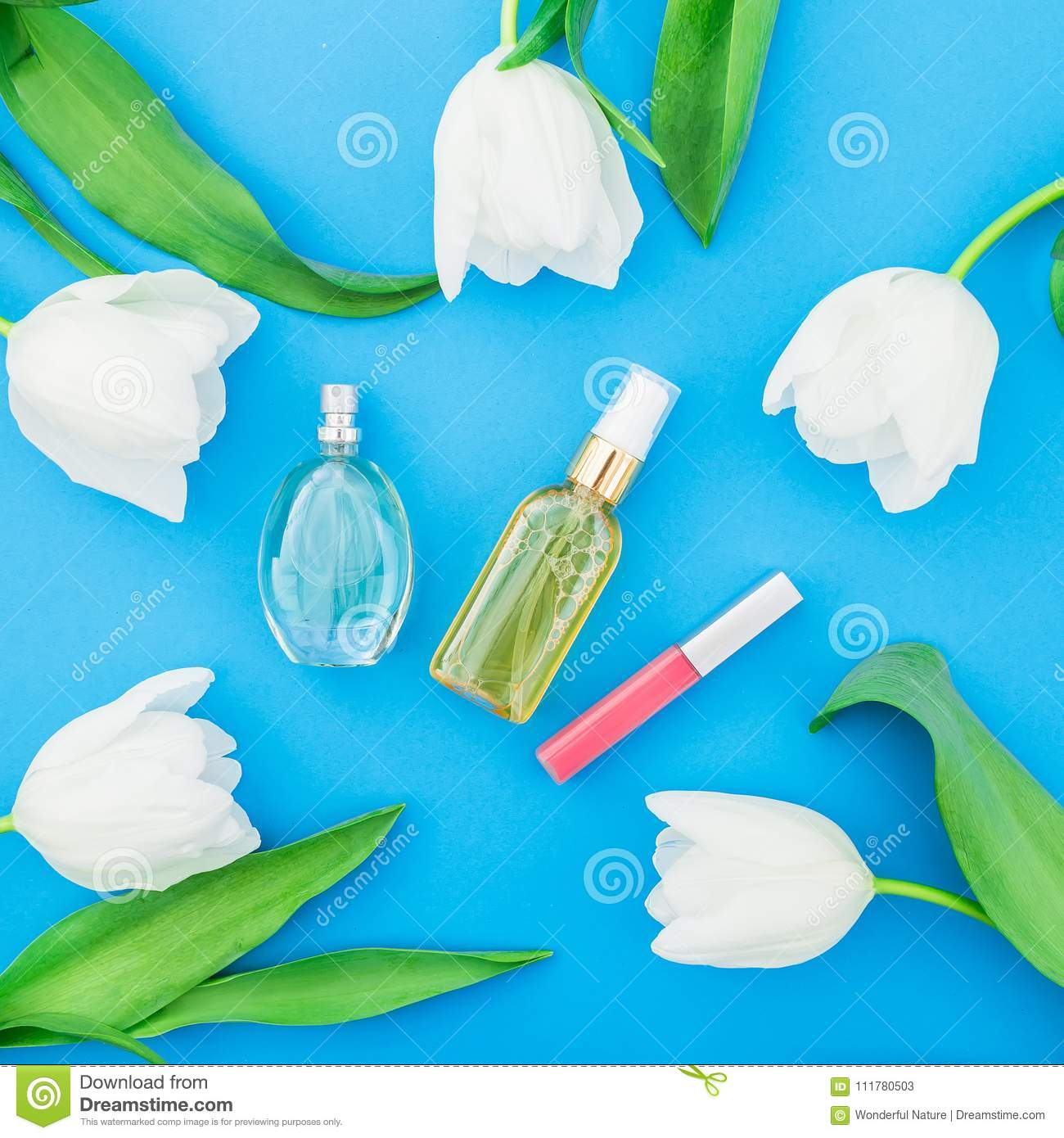 Feminine perfume, lipstick and white tulips flowers on blue background. Beauty blog. Flat lay, top view