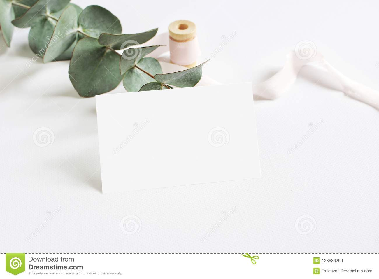 Feminine stationery mockup scene with a paper greeting card, spool of pink silk ribbon and Silver dollar eucalyptus