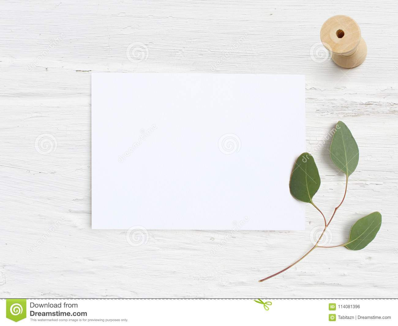 Feminine wedding desktop mock-up with blank paper card, wooden spool and Eucalyptus populus branch on white shabby table