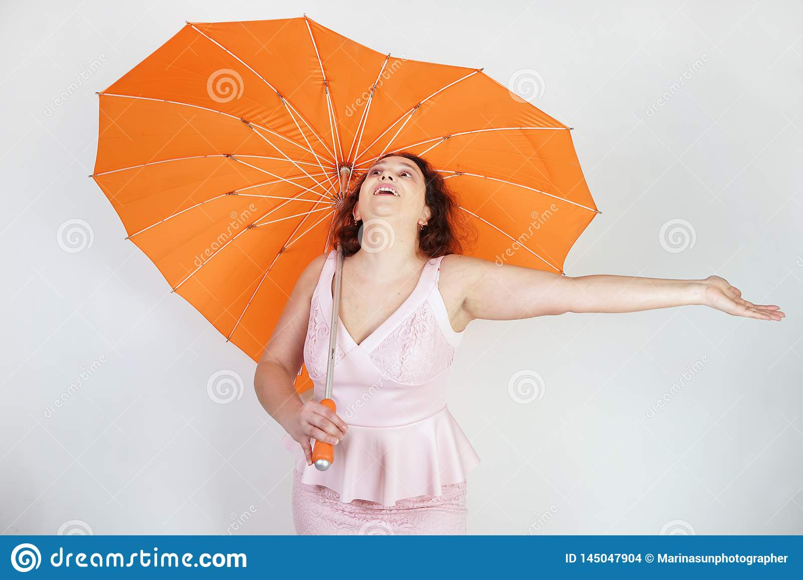 Feminine woman with plus size body in pink dress with orange big heart shaped umbrella posing on white background in Studio