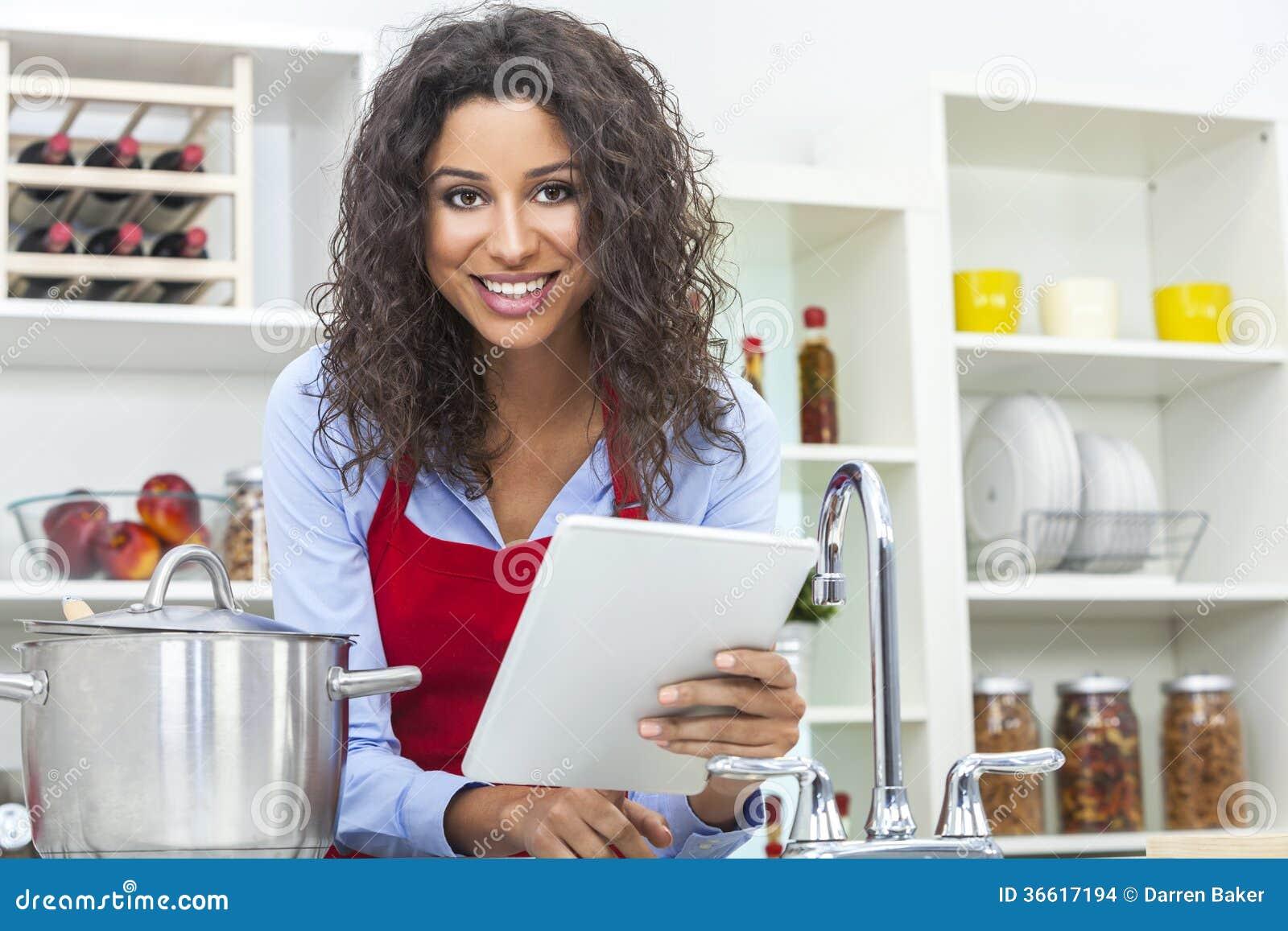 Femme l 39 aide de la tablette faisant cuire dans la for Aide de cuisine