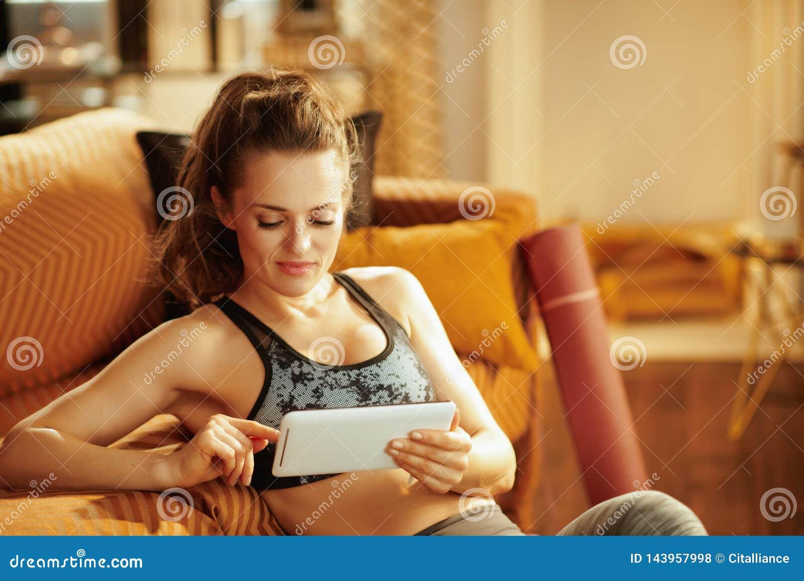 Femme à l aide de la tablette pour partager des résultats de séance d entraînement dans des médias sociaux