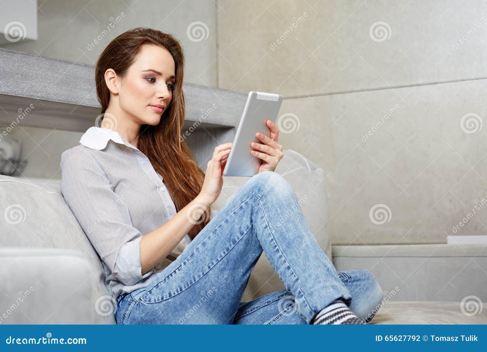 Femme à l aide du comprimé numérique sur le sofa