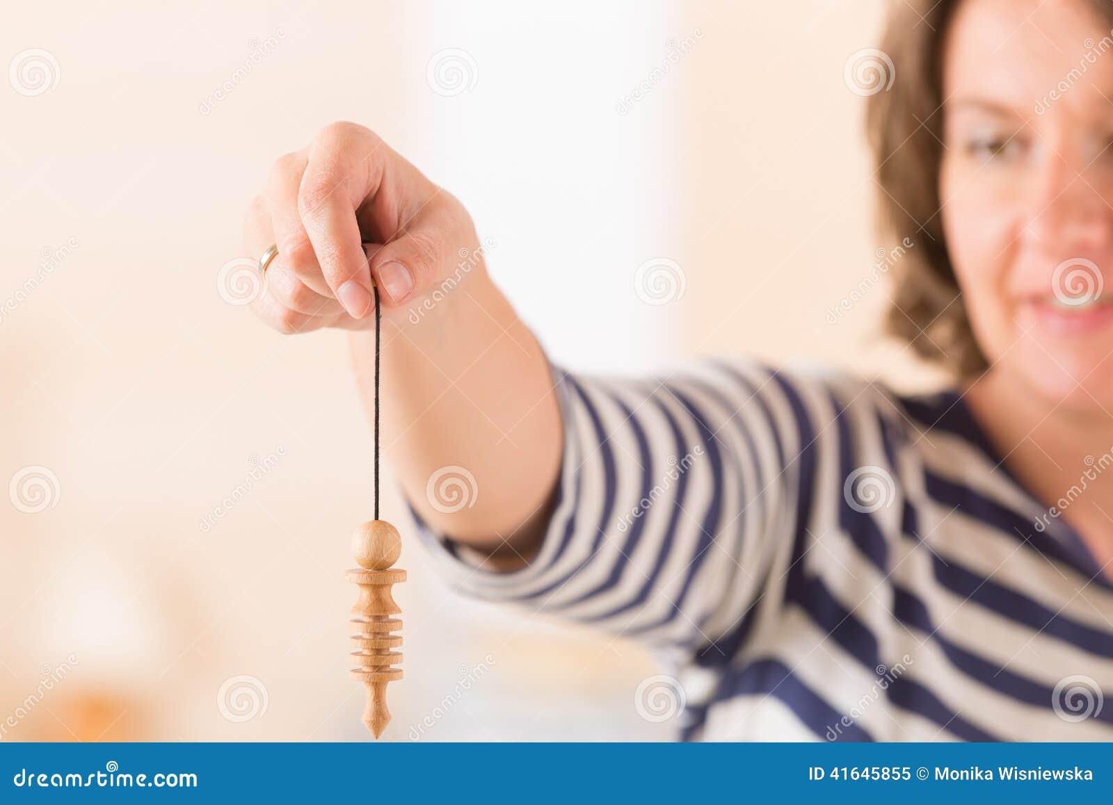 Femme à l aide du pendule