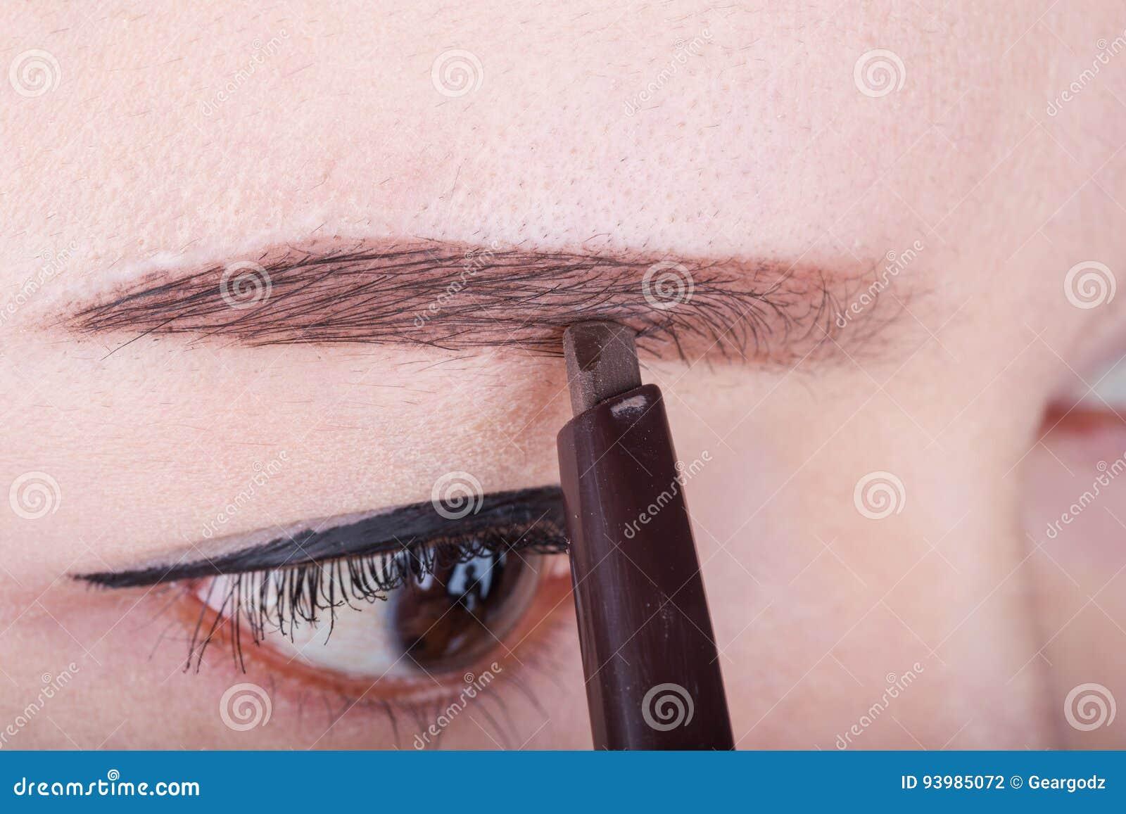 Femme à l aide du sourcil de maquillage de crayon