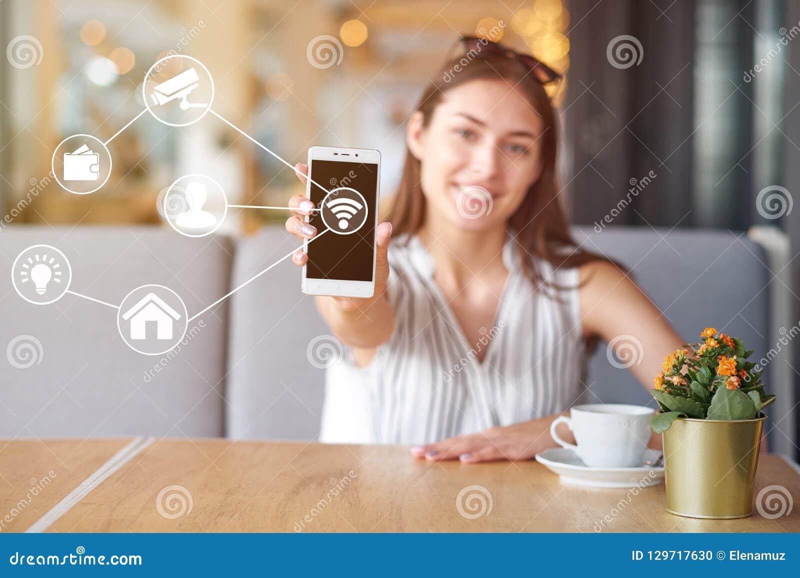 Femme à l aide du téléphone intelligent mobile moderne se reliant aux applis d automation de wifi Contrôle virtuel à distance à l