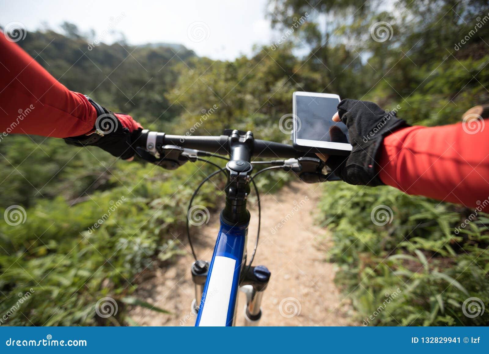 Femme à l aide du téléphone portable tout en montant le vélo