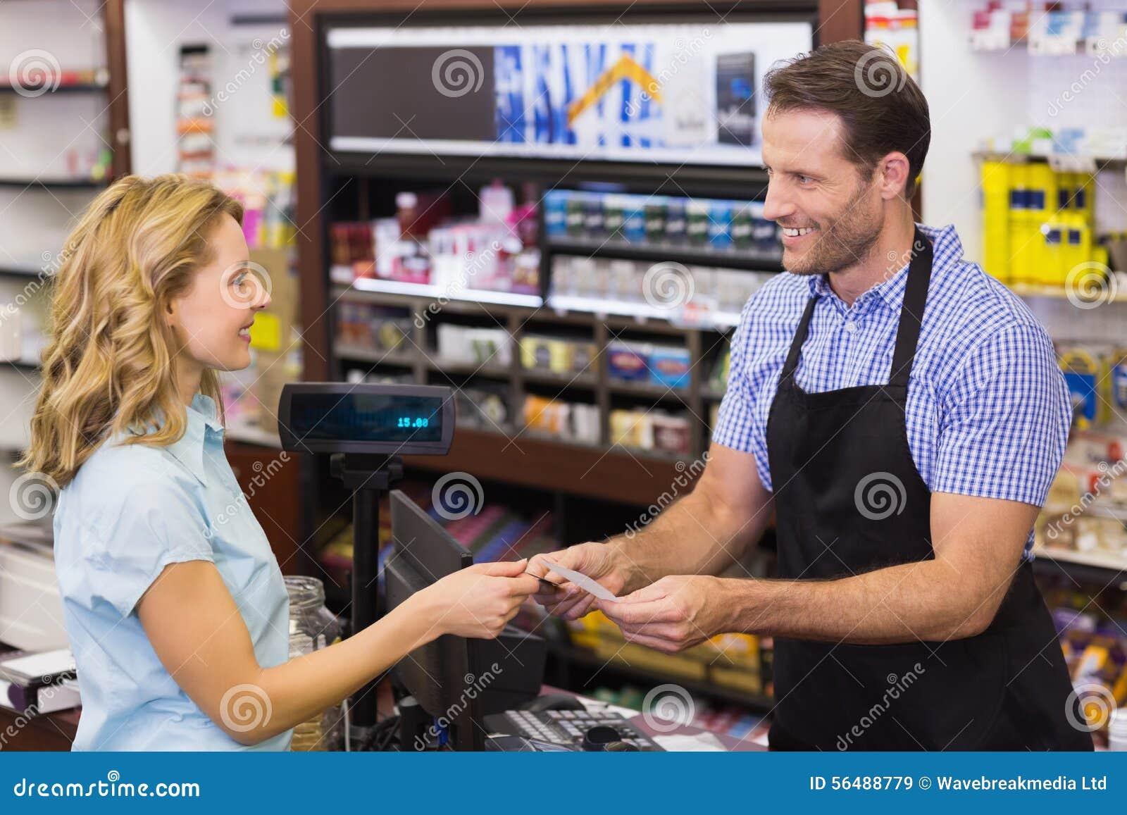 Femme à la caisse enregistreuse payant avec la carte de crédit
