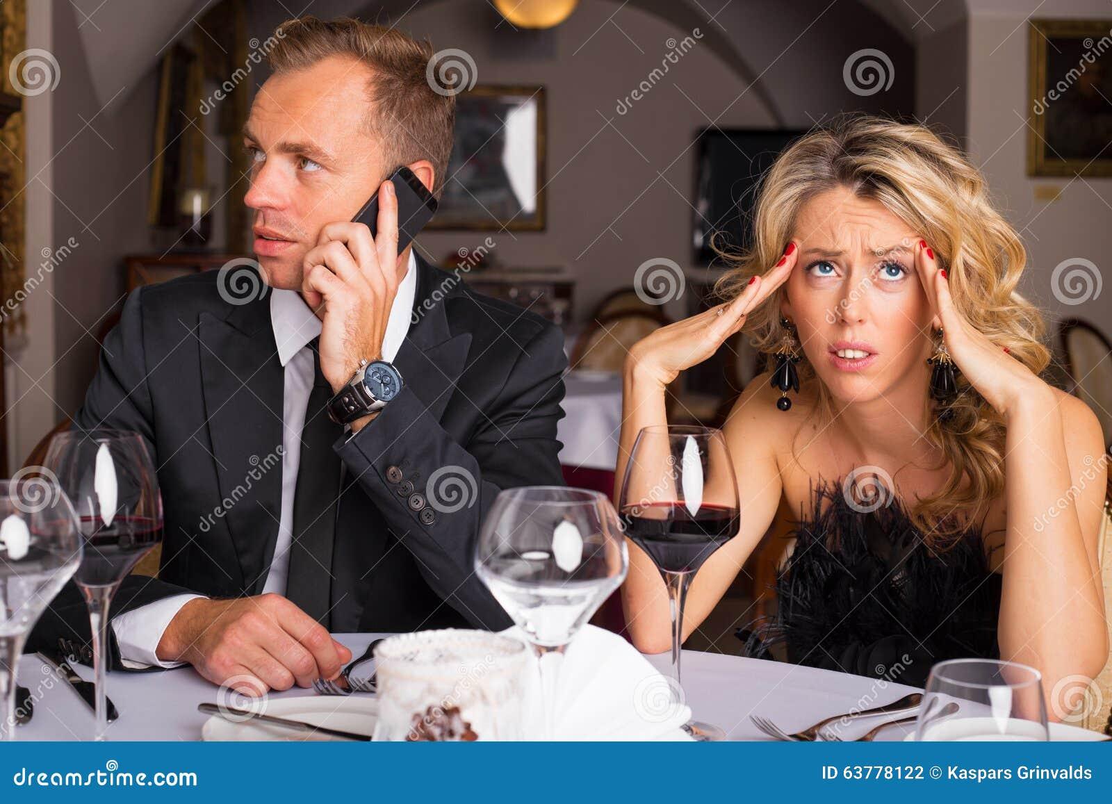 Femme à la date de dîner étant ennuyée de l homme parlant au téléphone