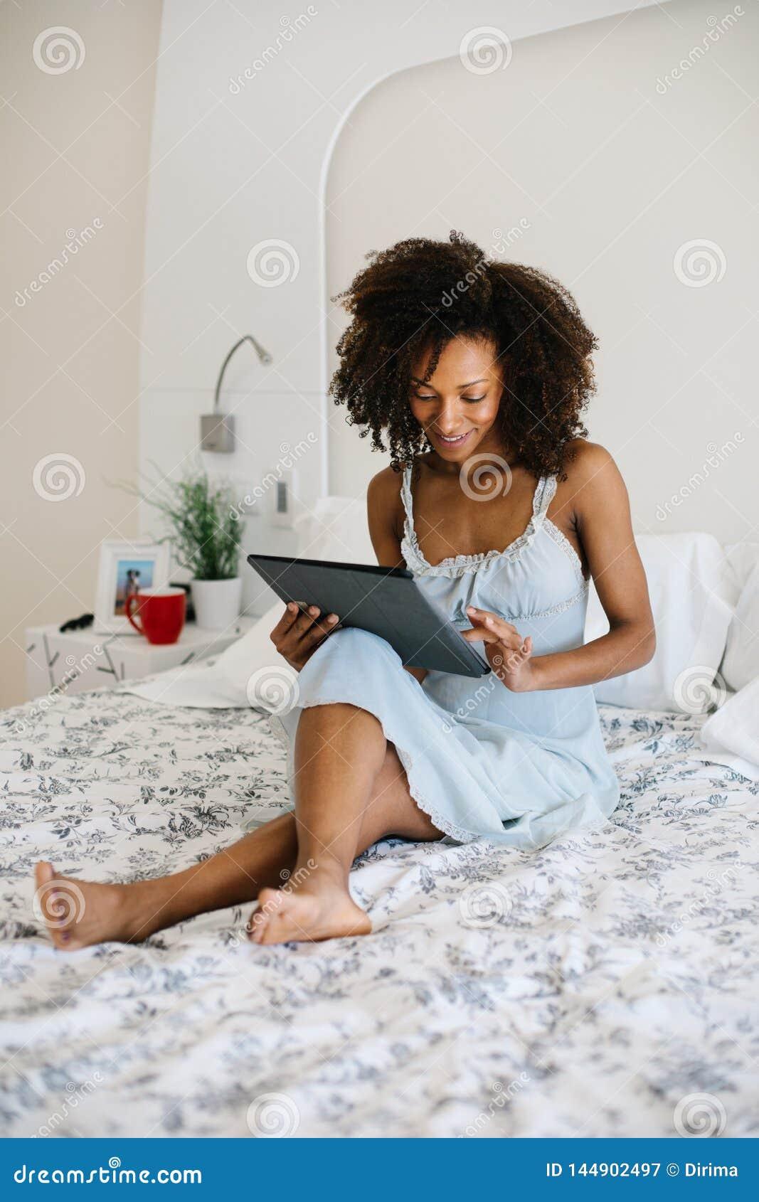 Femme à la maison lisant sur le comprimé numérique