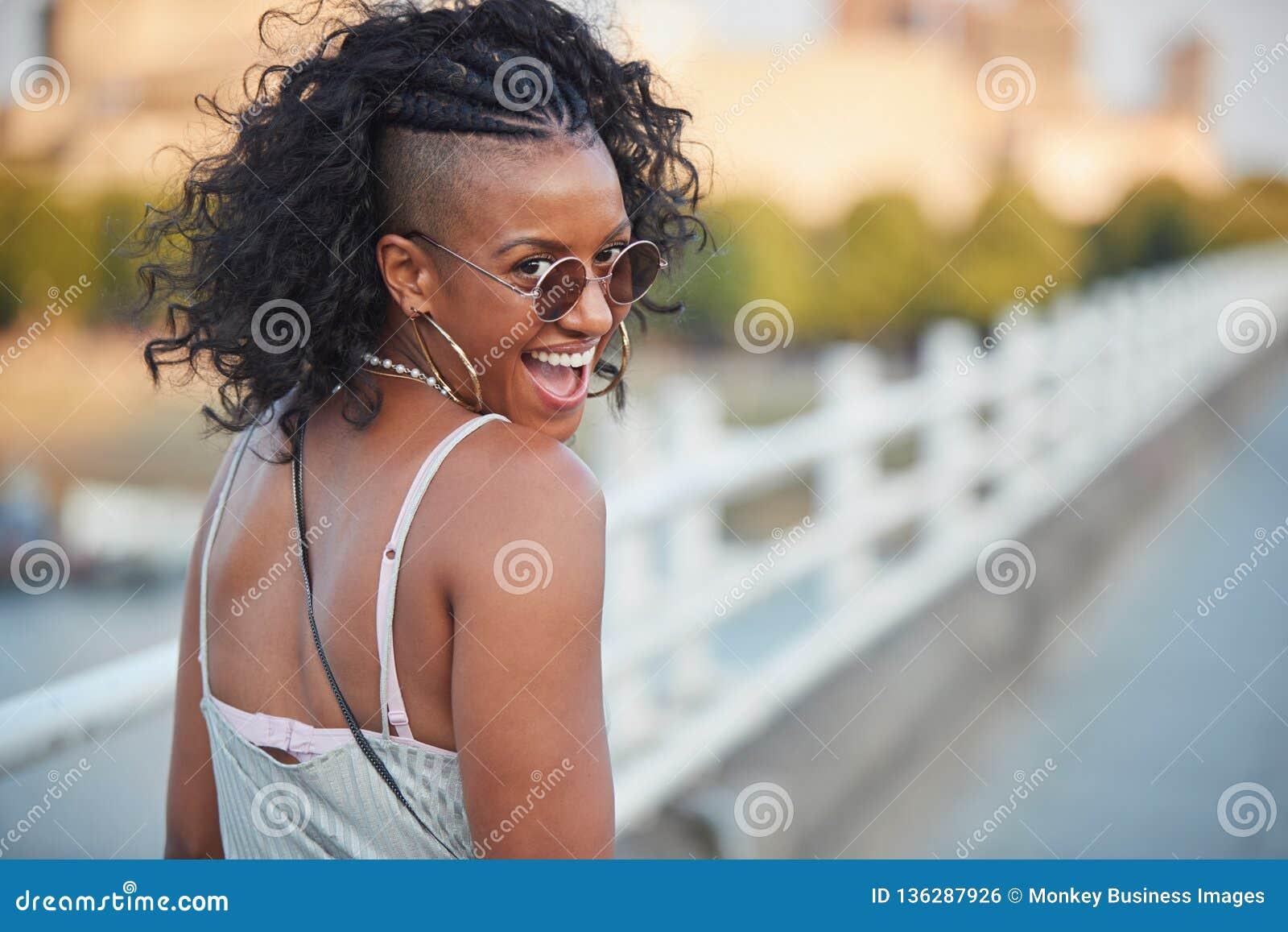 Femme à la mode dans la camisole rayée et des lunettes de soleil, tournant