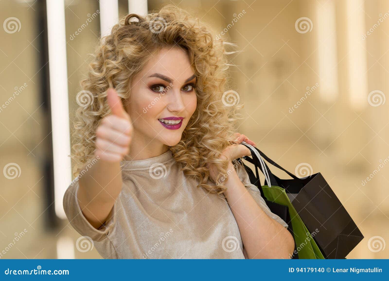 Femme à la mode habillée avec des paniers montrant des pouces dans le mail