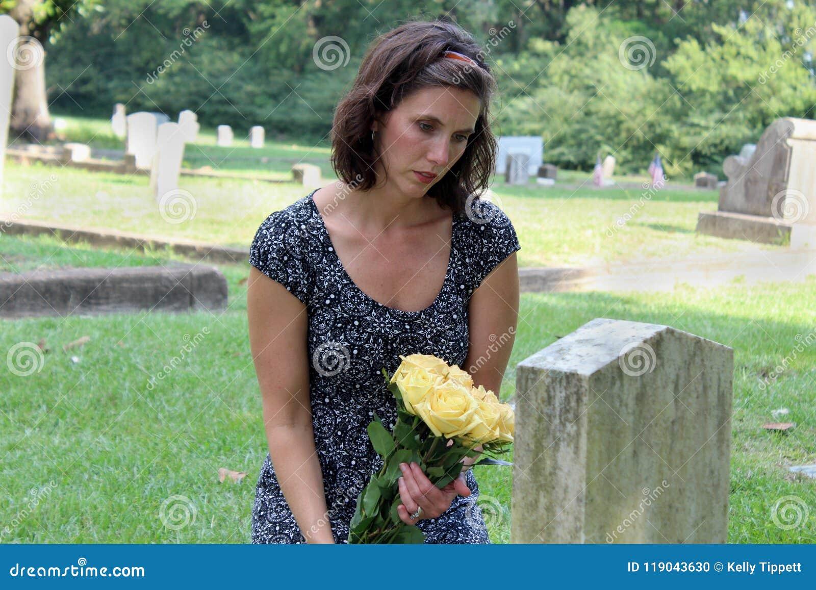 Femme à la pierre grave avec les fleurs jaunes
