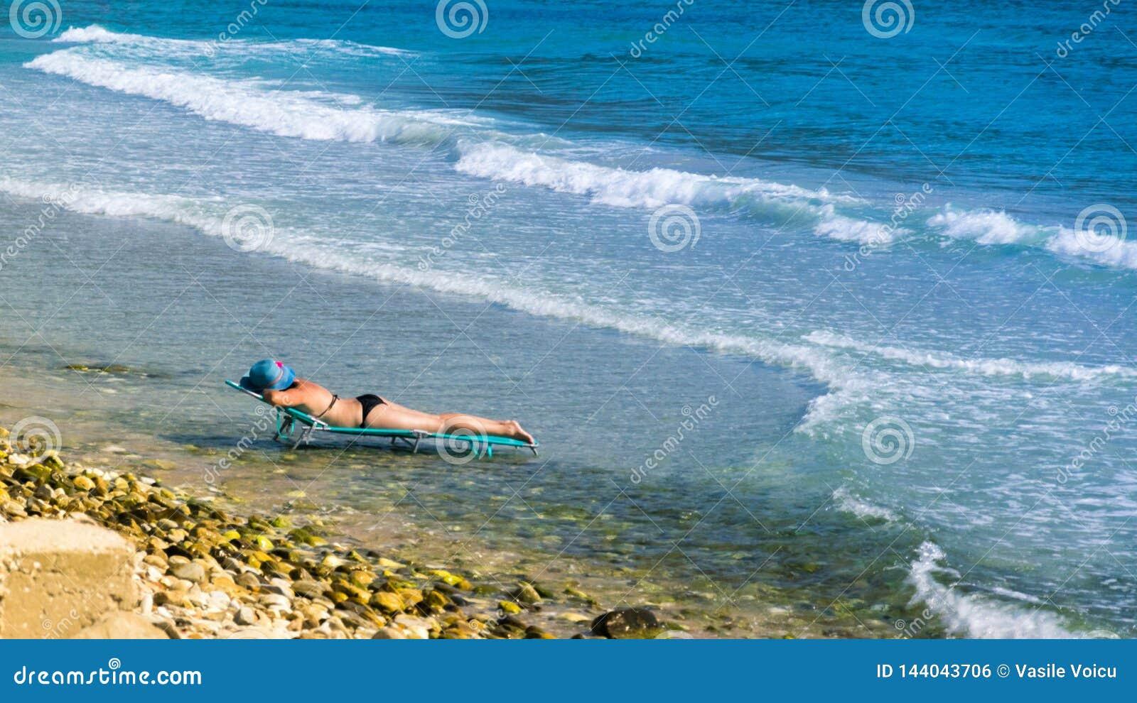 Femme à la plage sur la chaise longue, au milieu de l eau, au bord de la mer et à l océan, avec le chapeau bleu et la mer avec
