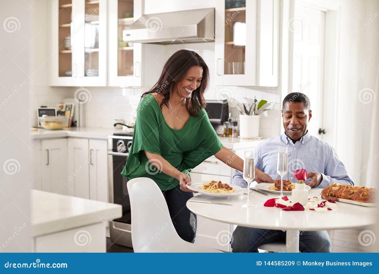Femme âgée moyenne de femme d Afro-américain servant à son associé un repas romantique dans leur cuisine, foyer sélectif