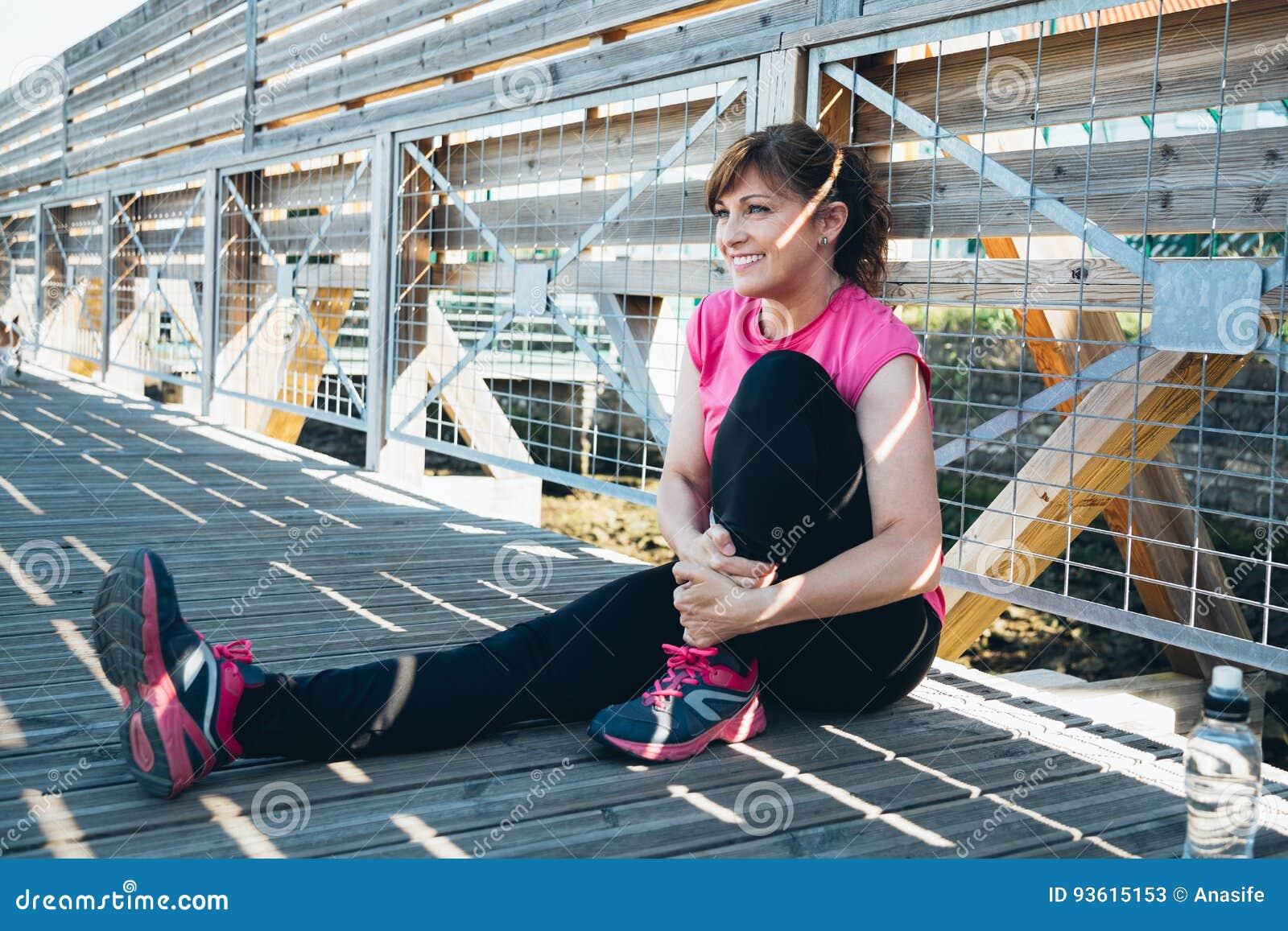 Femme âgée par milieu faisant étirant des exercices