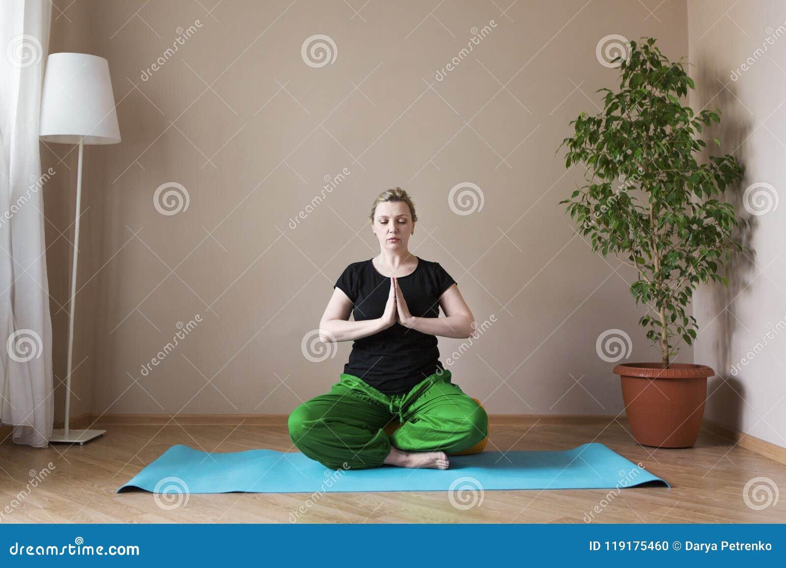 Femme âgée par milieu faisant le yoga à l intérieur