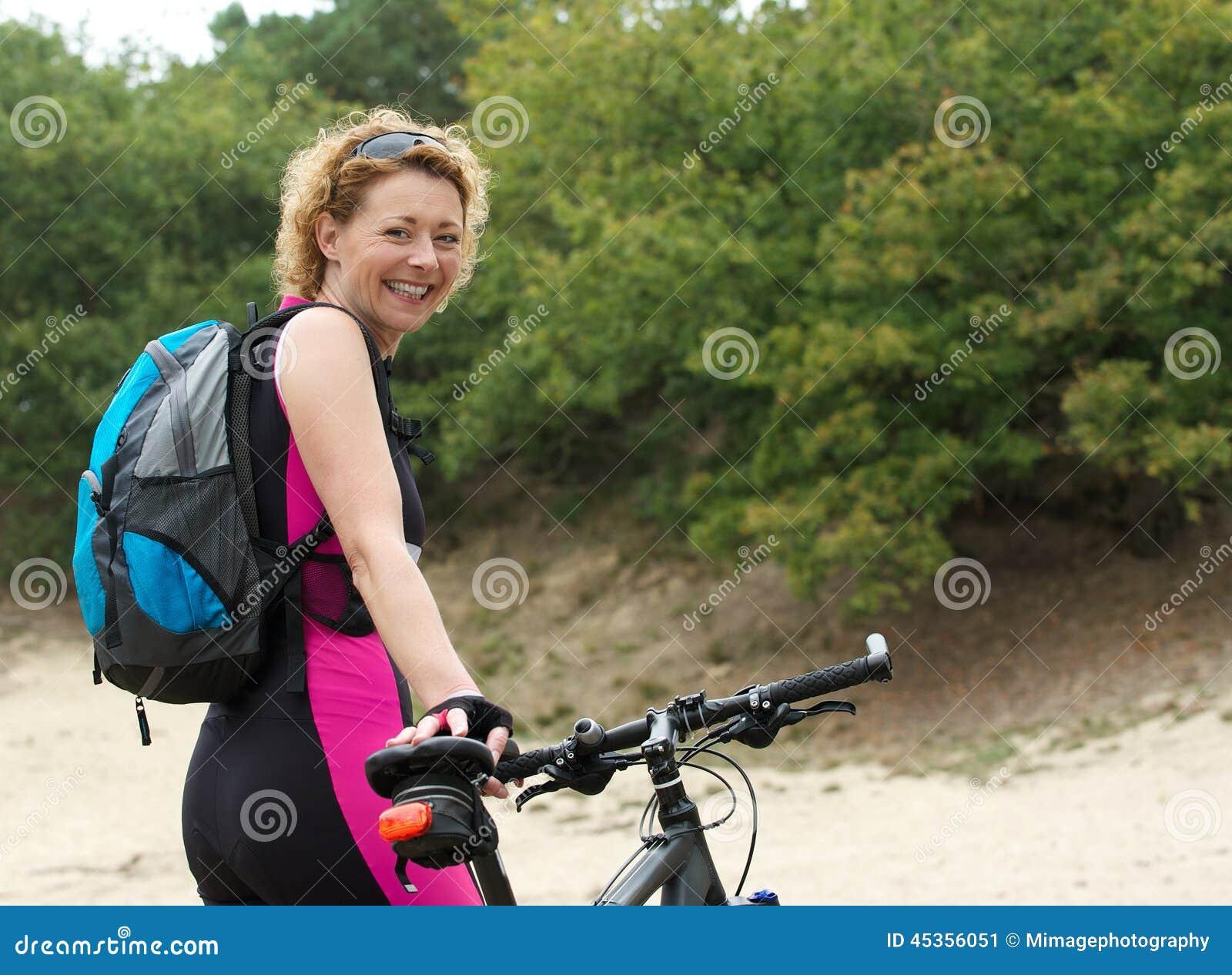 Femme âgée par milieu souriant avec le vélo
