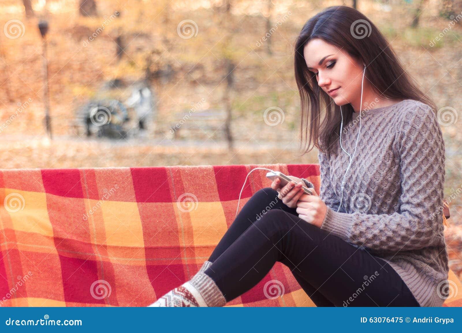 Download Femme écoutant La Musique Sur Un Banc Image stock - Image du expression, fille: 63076475