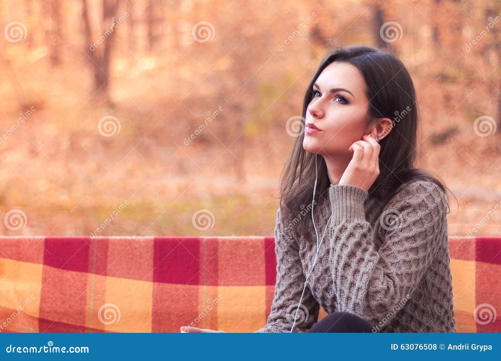 Download Femme écoutant La Musique Sur Un Banc Photo stock - Image du orange, forêt: 63076508