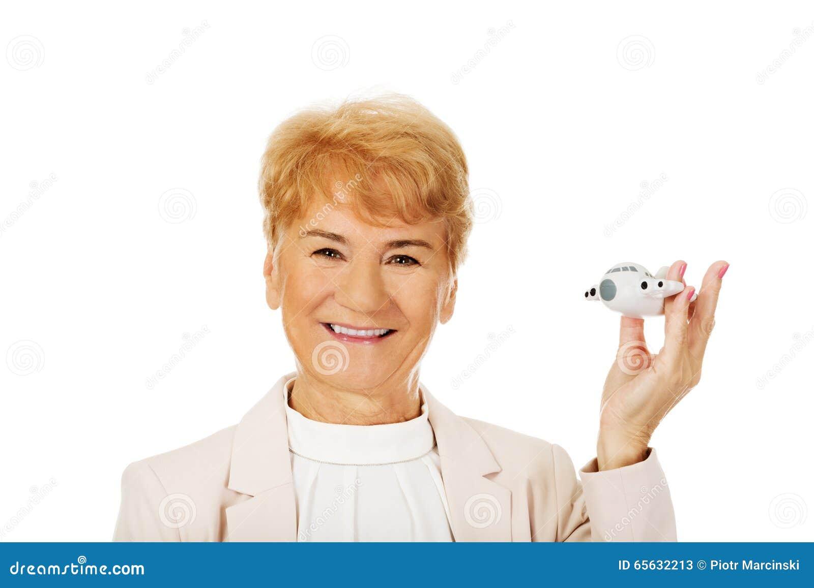 Femme élégante pluse âgé de sourire tenant un avion de jouet
