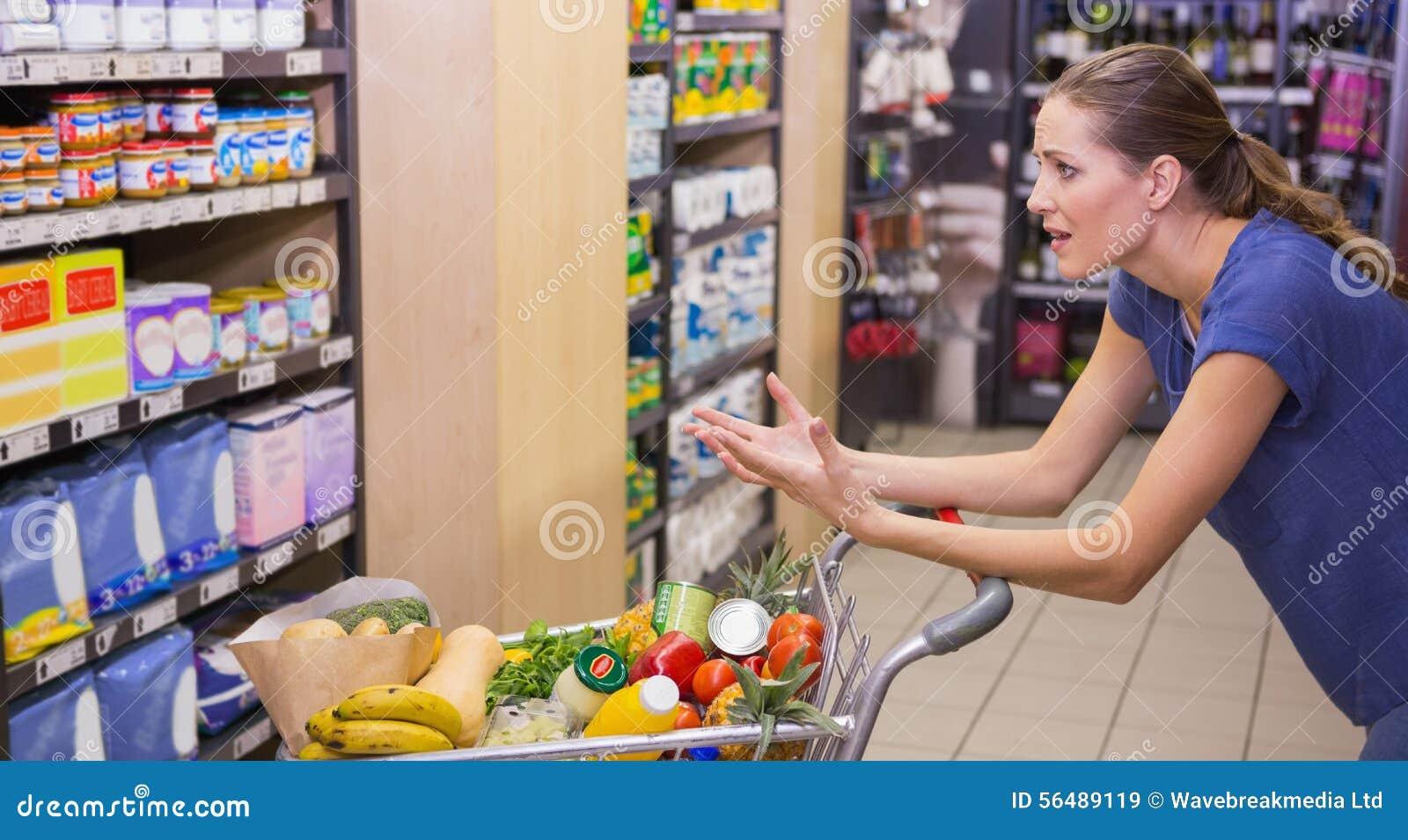 Femme étonnée regardant le produit sur l étagère
