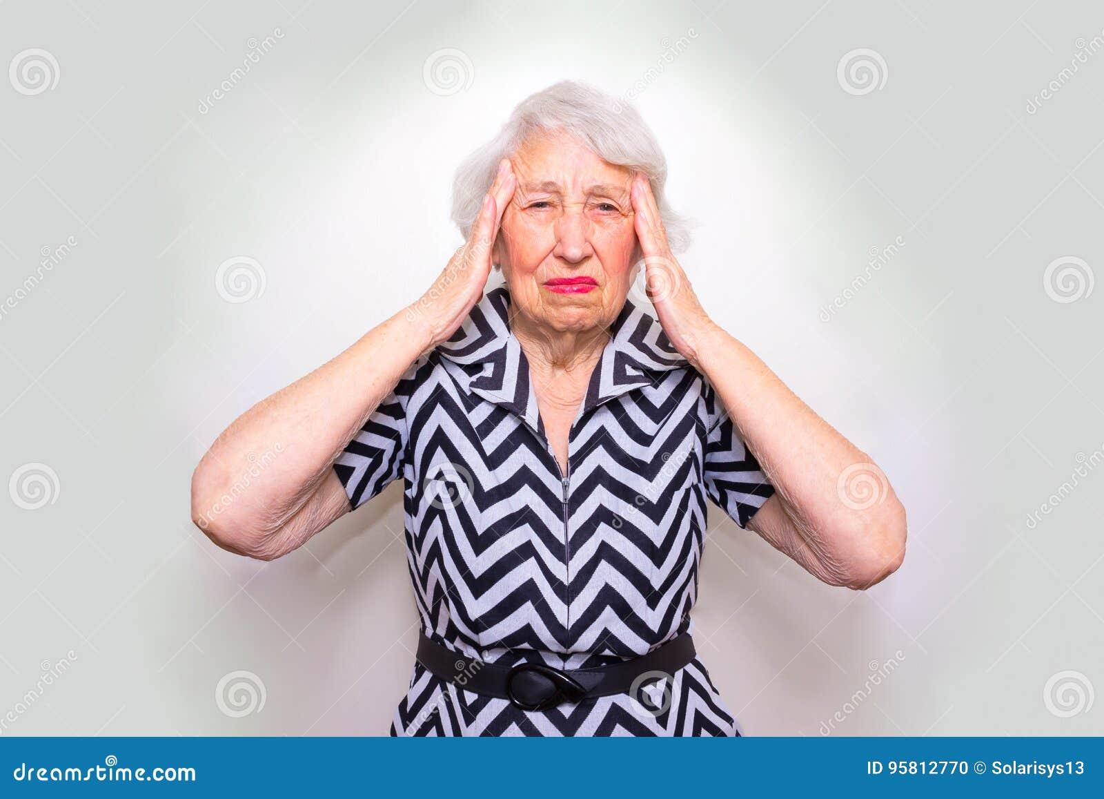 Femme aîné avec la tête dans des mains semblant lasses