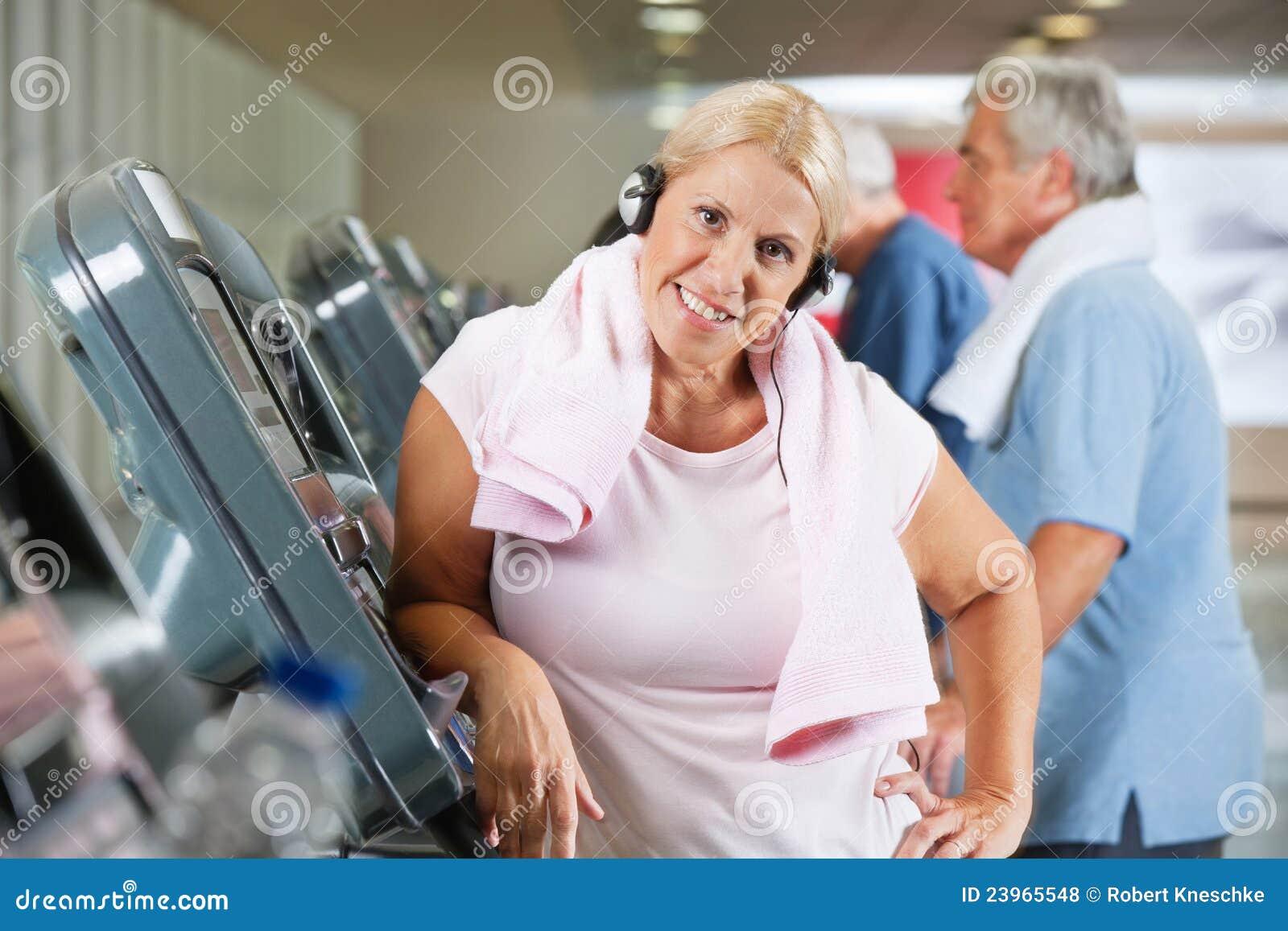 Femme aîné sur le tapis roulant en gymnastique