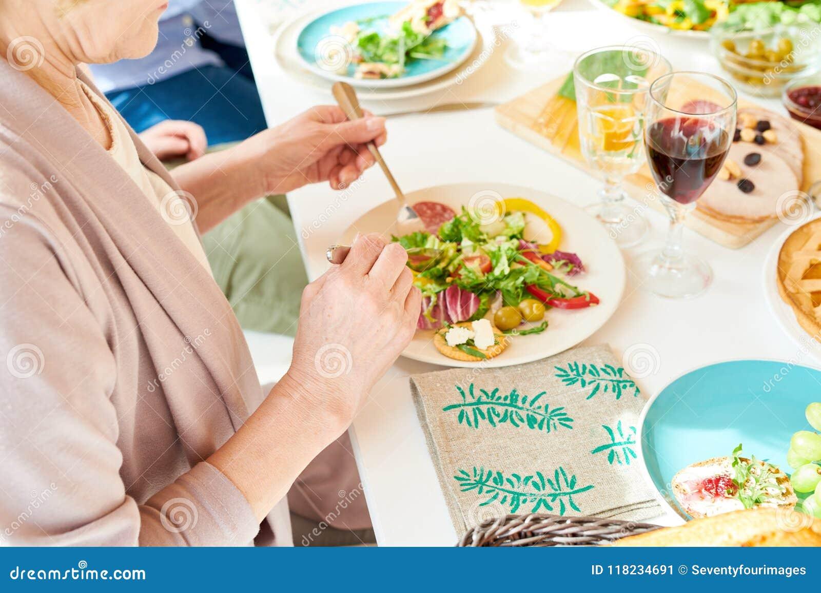 Femme aînée mangeant de la salade