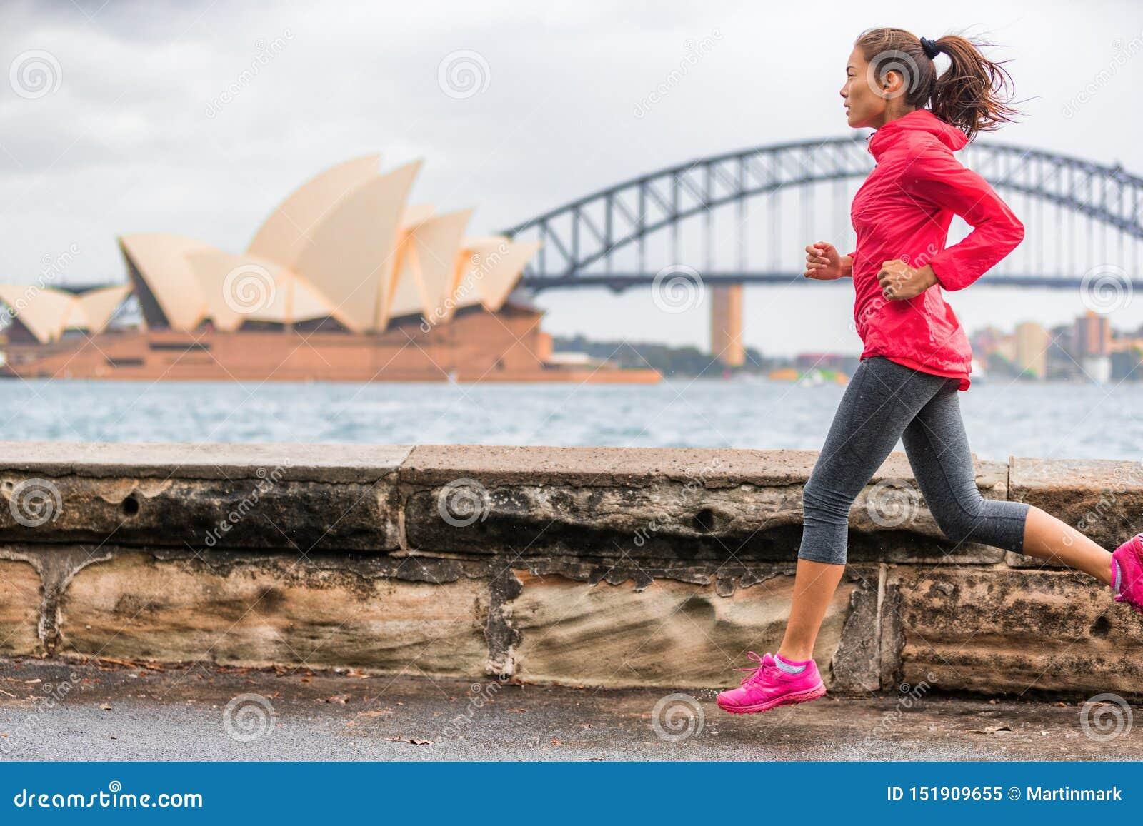 Femme active de mode de vie d ajustement de coureur pulsant sur Sydney Harbour par le point de repère célèbre d attraction touris