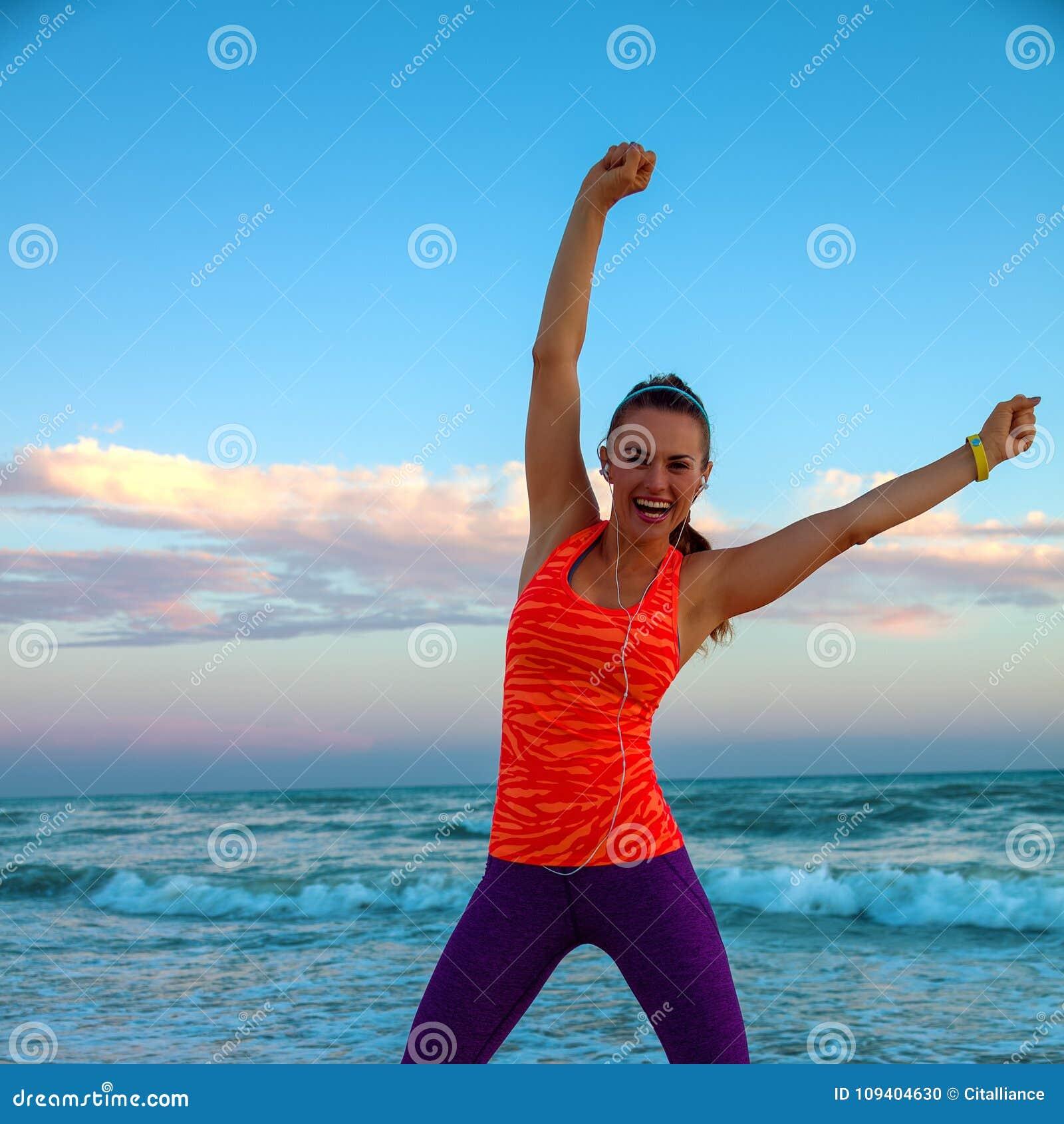 Femme active heureuse sur le bord de la mer à la réjouissance de coucher du soleil