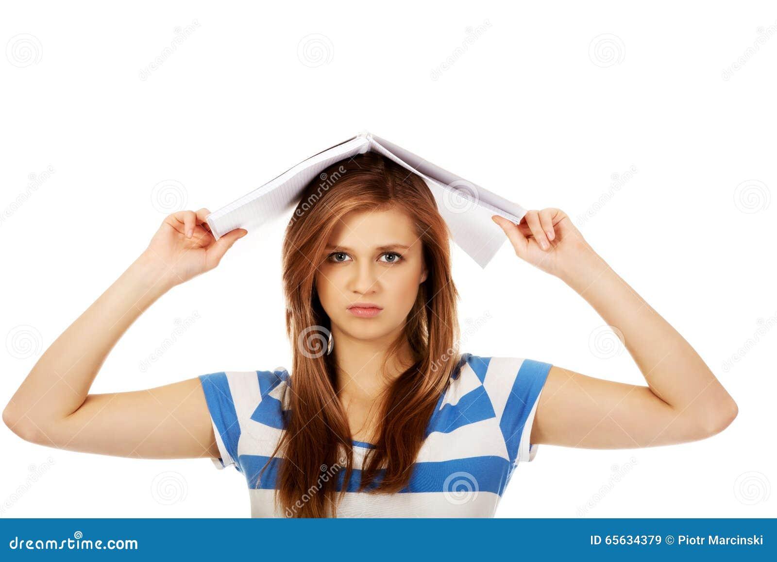 Femme adolescente avec le carnet sur la tête
